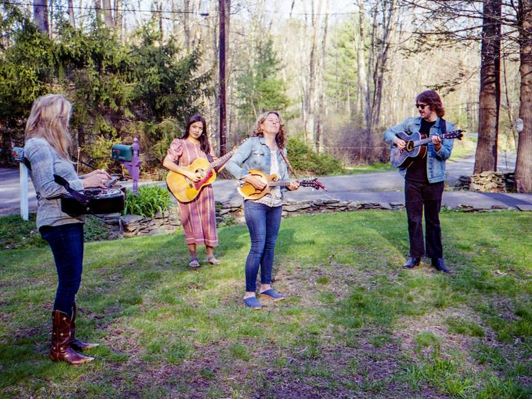 Amy Helm and the Curbside Pickup Band playing music on a front lawn.