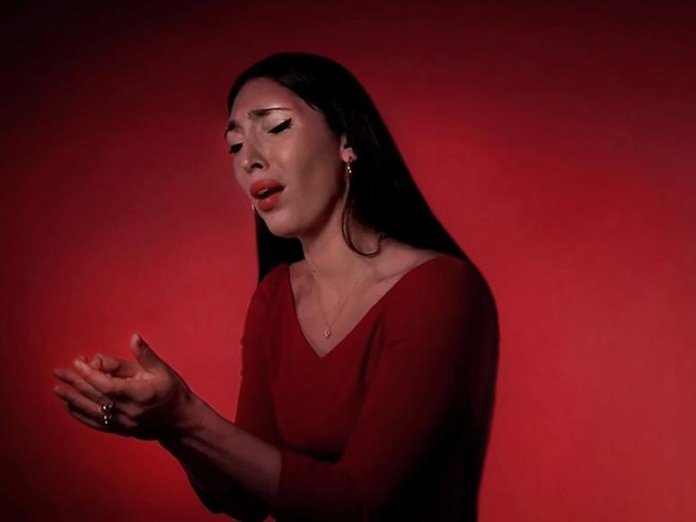 Laura Baldassari on a red background, singing.