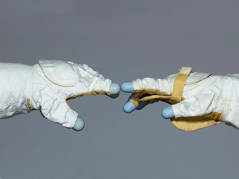Two astronaut gloves touching on a grey background.