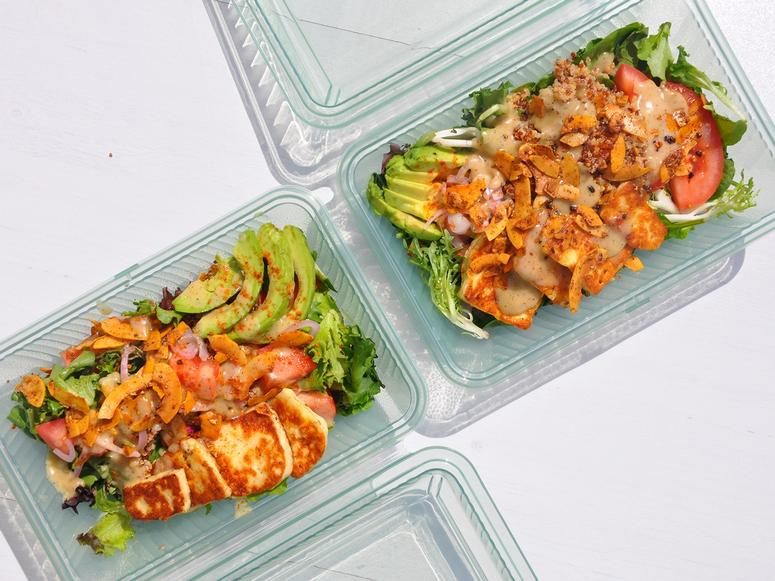 Two Case containers with multicolored salads inside.