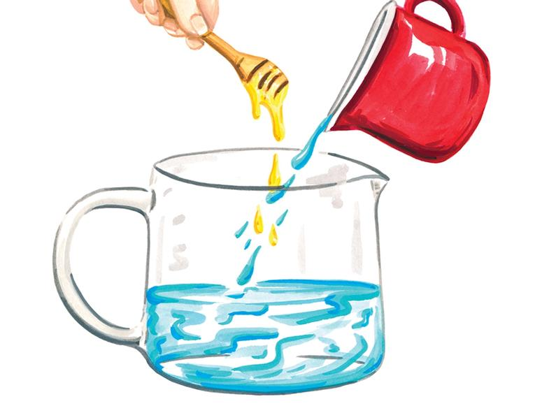 A pitcher of water with a hand holding a honey wand overhead.