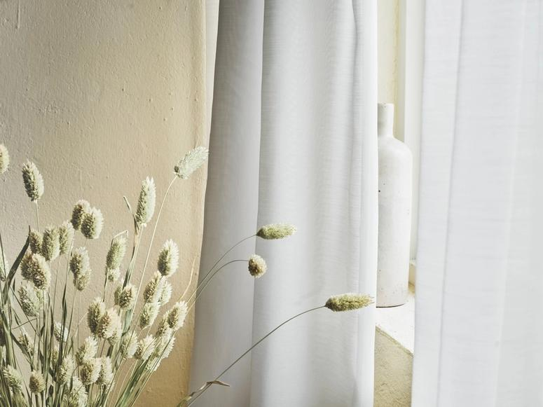 White curtains in front of stalks of wheat.