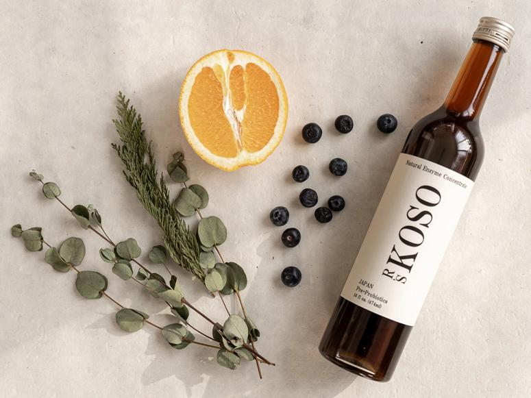 A bottle of R's Koso next to blueberries, half an orange, and herbs.