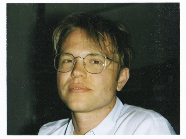 Caius Pawson in glasses with disheveled hair.