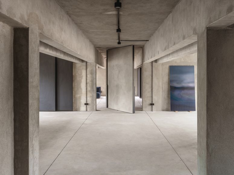 A view into an empty concrete interior with a revolving door at its center
