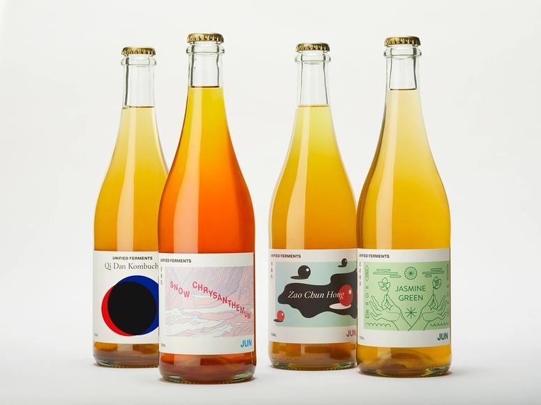 Four yellow and orange bottles of Unified Ferments teas on a white background.