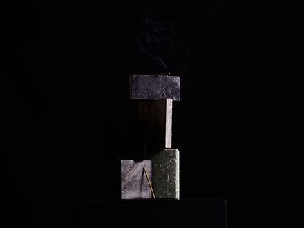 A stick of incense balanced with four pieces of stone