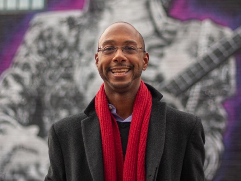 Author and scholar Elliott H. Powell with a red scarf in front of a mural.