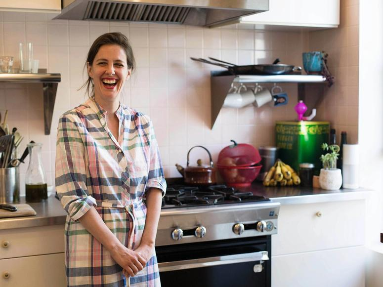 Mina Stone laughing in her kitchen.