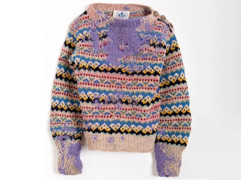 An old sweater darned with purple thread.