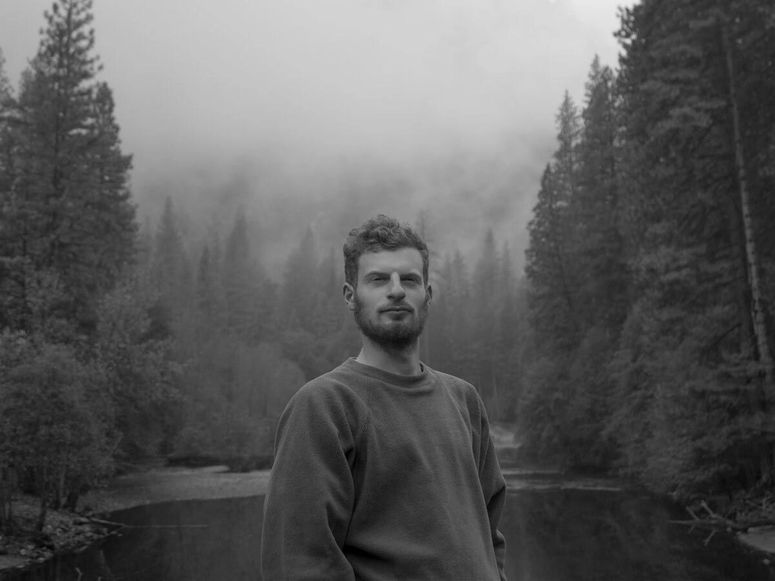 Photay in a black and white photograph taken in the woods, in front of a small lake.