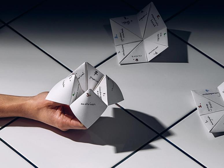 A hand holding a paper origami fortune teller
