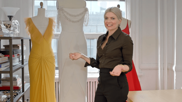 Stylist Kate Young with three red carpet dresses on mannequins