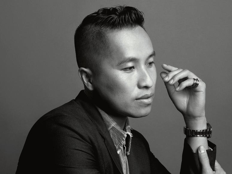 Fashion designer Phillip Lim in profile, in a suit, in a black and white photograph.