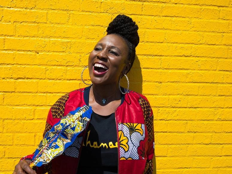 Toni Blackman laughing on a yellow brick background.