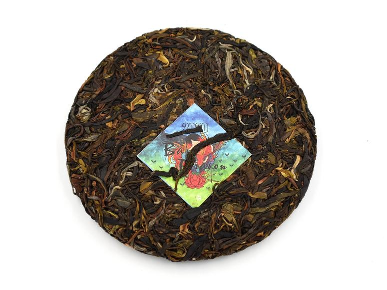 A cake of dried pu-erh with a colorful tag.