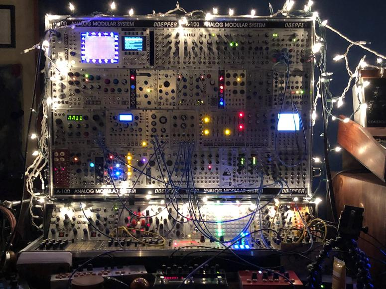 A large analog synthesizer covered in Christmas lights.