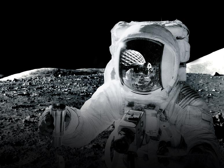 An astronaut on the moon, with a dome reflected in their visor.