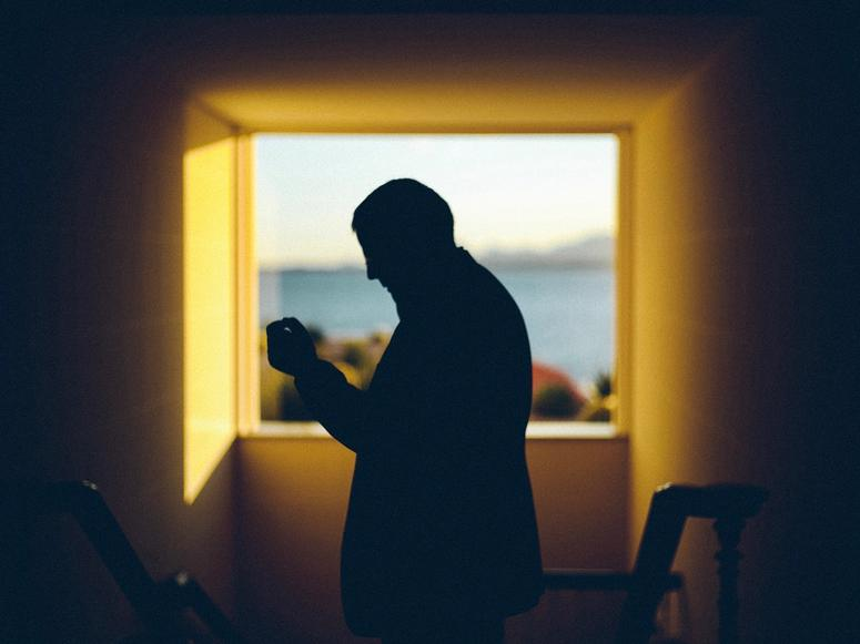 A man's silhouette sniffs perfume near a bright window.