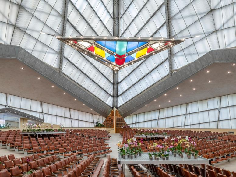 A large, open synagogue interior with a stained glass triangular chandelier.