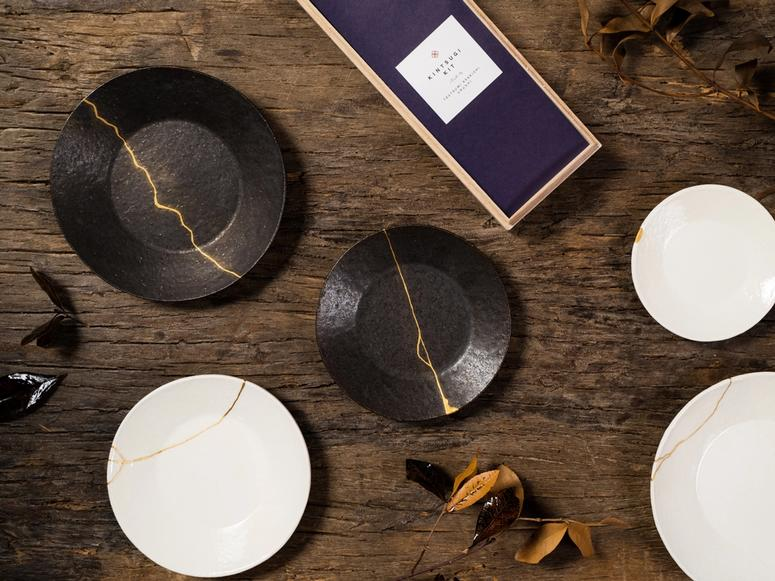 A kintsugi kit on a wooden table, next to several repaired plates.