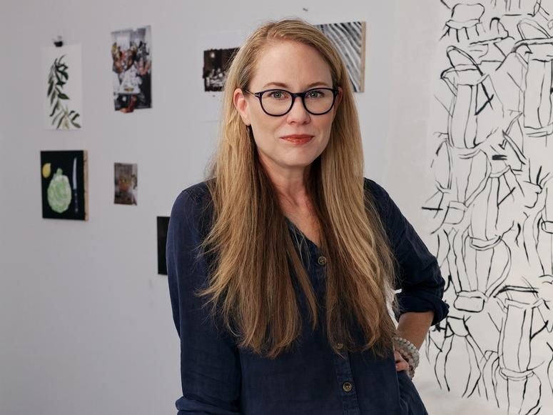 Catherine Haley Epstein stands with her hand on her hip in front of several drawings.
