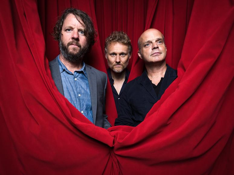 Martin, Wood, and Medeski in red theater curtains.