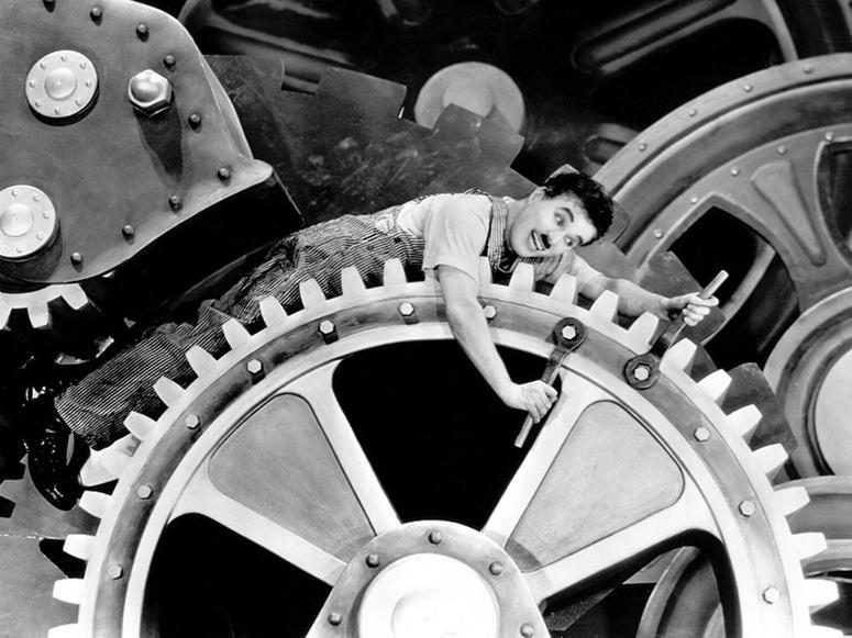 Charlie Chaplin riding the gears of a massive machine.