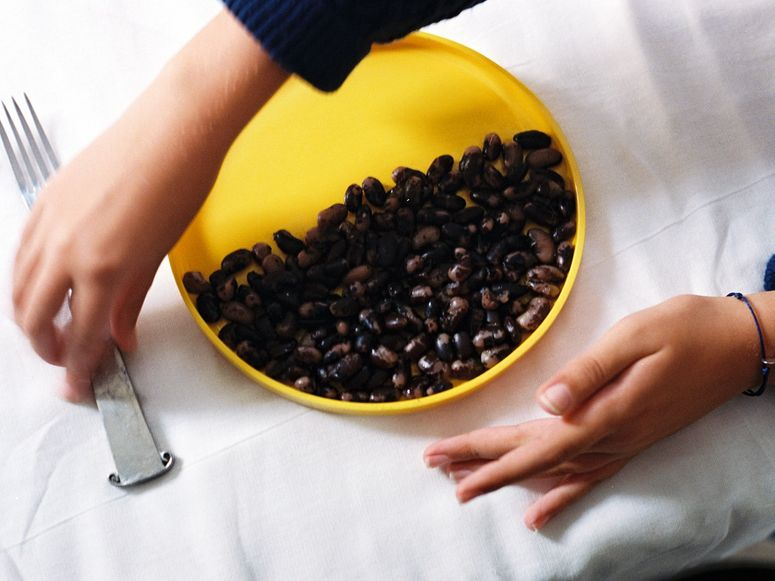 A yellow plate half filled with black beans.