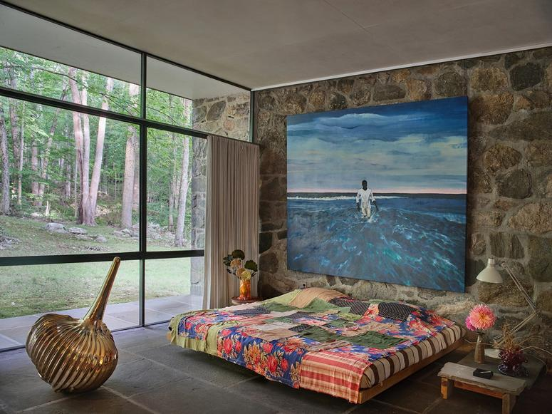 A bedroom at the Eliot Noyes House, with a large blue painting, multicolored bedspread, and brass sculpture near a large glass window.