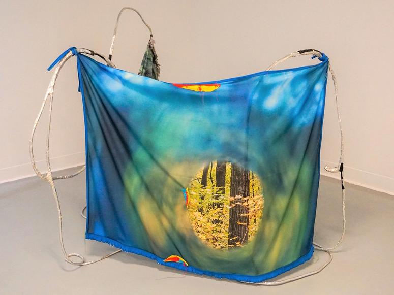 A blue printed textile hung with aluminum wire in an art gallery.