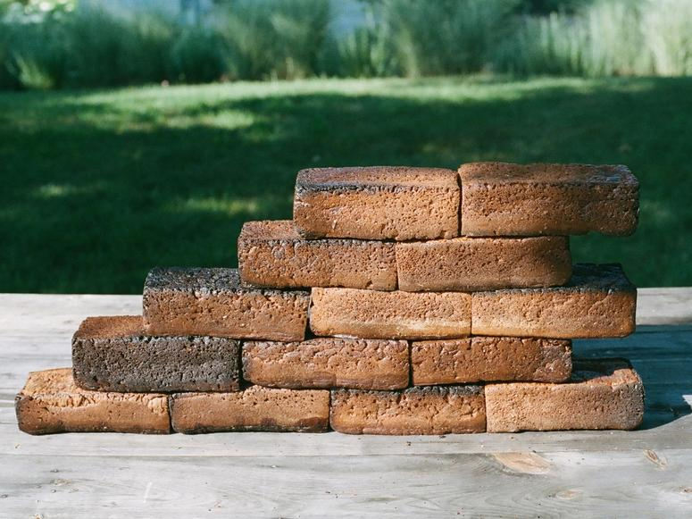 A stack of brick-like bread loaves with a green lawn in the background.