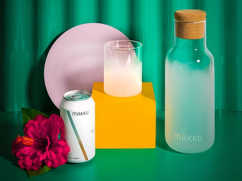 A carafe, glass, and can of Makku on a green backdrop.
