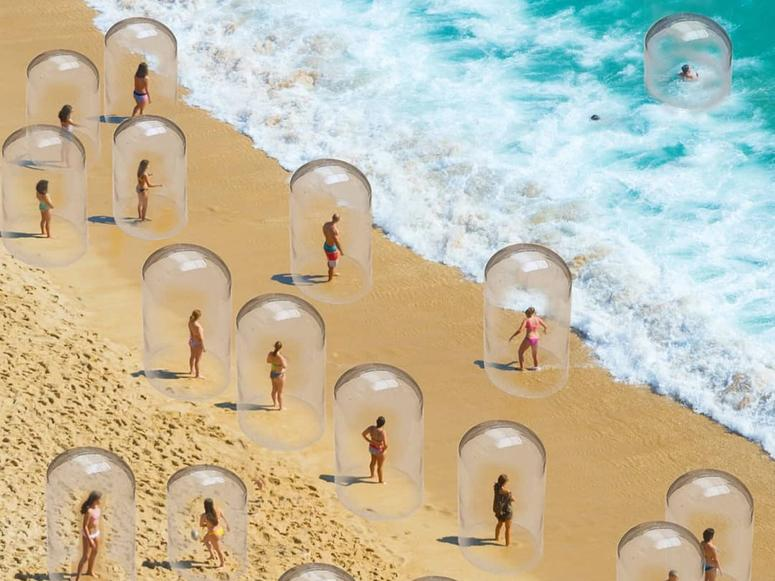 Various people encased in glass bubbles stand on the beach near the ocean
