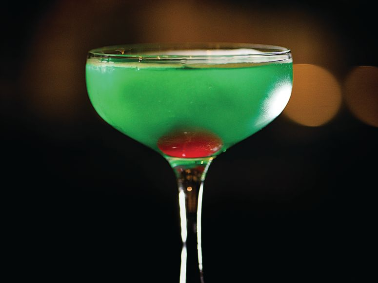 A martini glass with green drink and cherry inside