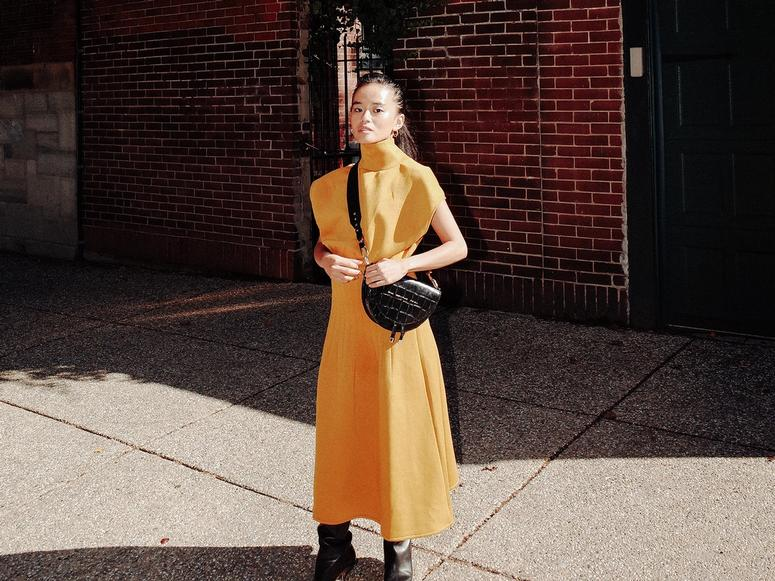 Olivia Lopez in a yellow dress, with a black leather handbag.