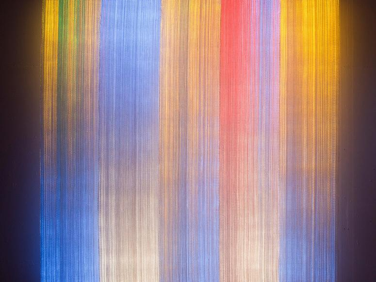 A textile in bright streaks of gold, blue, and red.