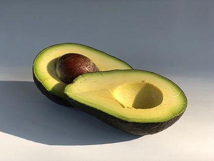 A split avocado in bright, moody lighting.