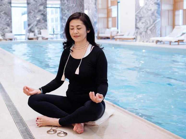 Snow Shimazu meditating next to a hotel pool.