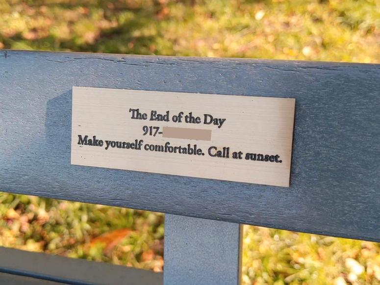 A bench with a gold plaque on it.