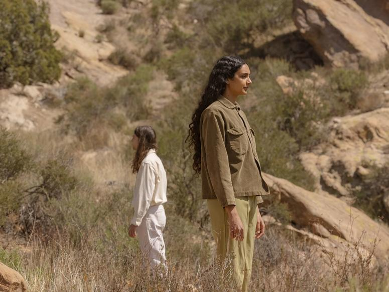 Junaco's two members facing opposite directions while standing in desert foothills.