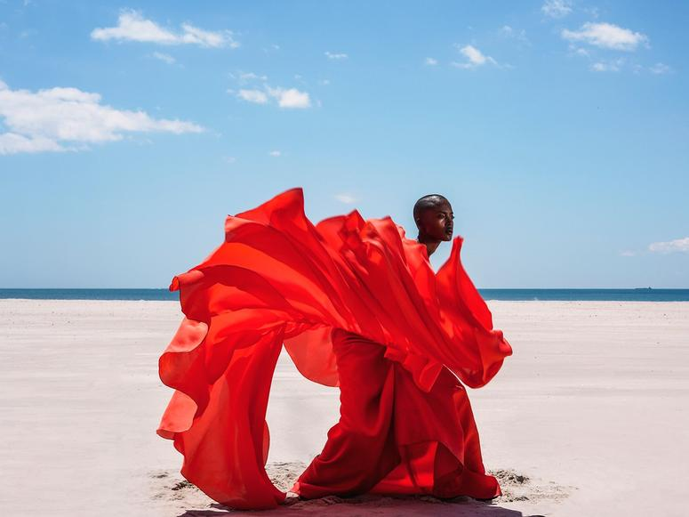 A photograph of a woman in a bright red dress on the beach.