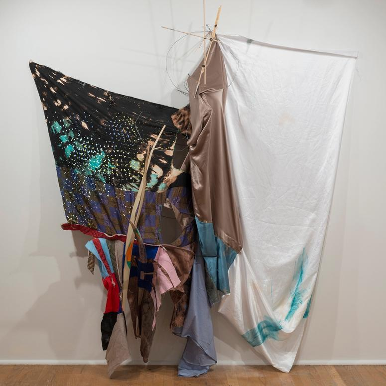 Artwork made from draped textiles and wood poles