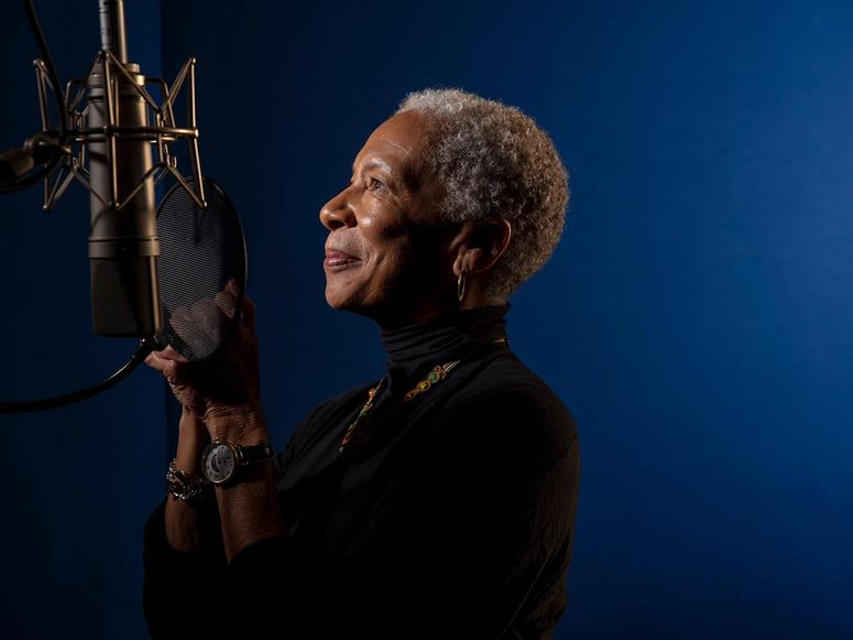 Angela Glover Blackwell looking into a microphone, in front of a blue background.