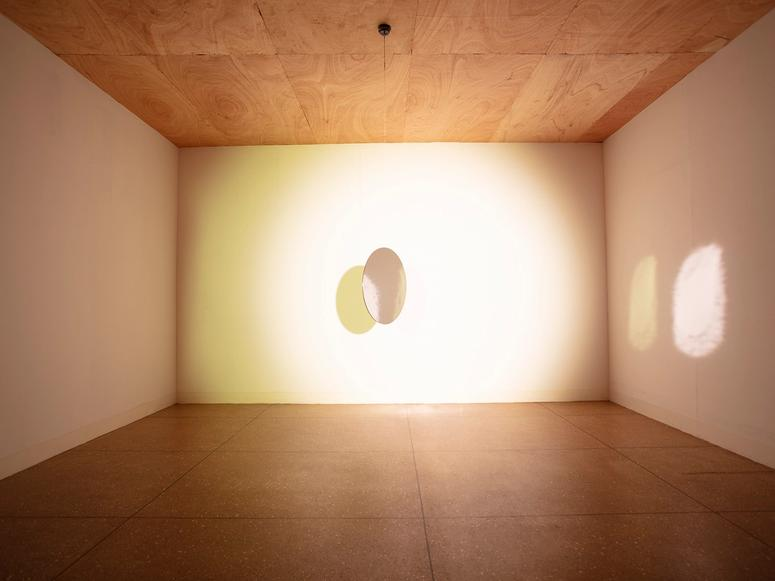 """Olafur Eliasson's installation """"Tell Me About a Miraculous Invention,"""" involving a mirror and light in a gallery."""