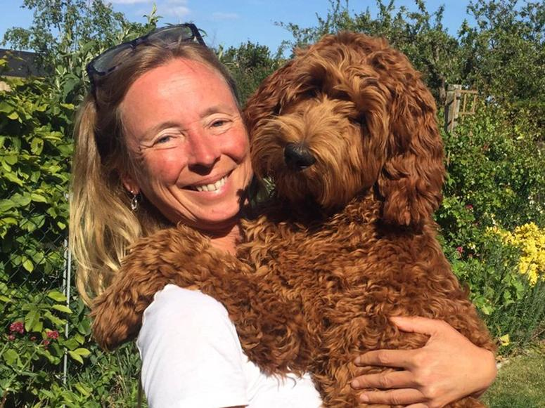 Dr. Kate McLean smiles and holds her dog in a garden.
