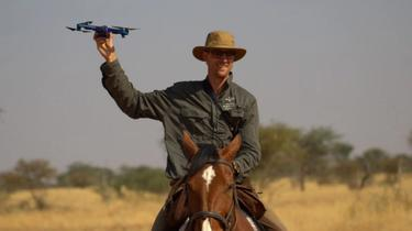 Friedrich monitoring wildlife from horseback, holding the Skydio 2.