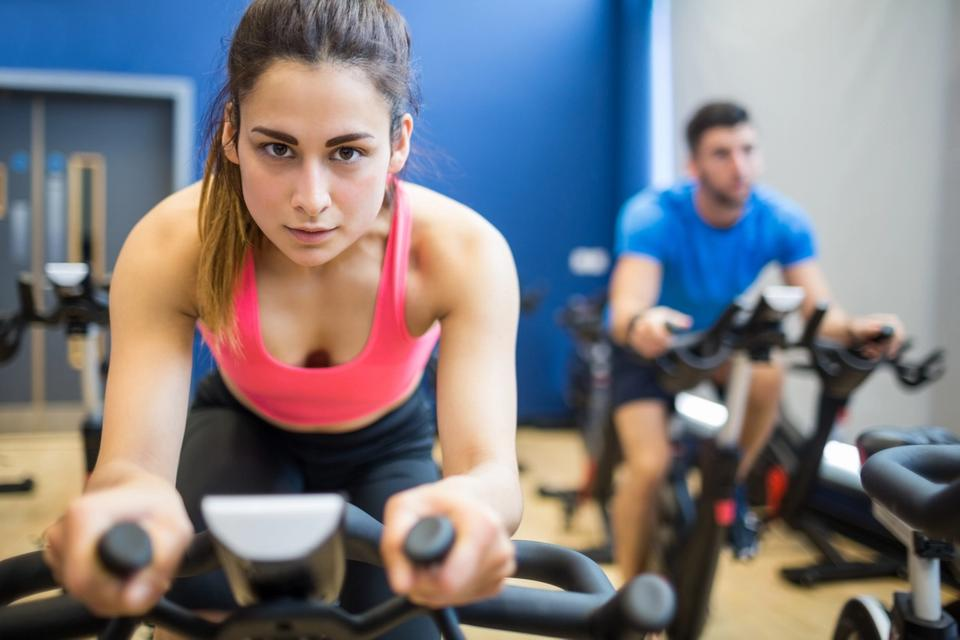 Couple doing spinning training on indoor cycling bikes