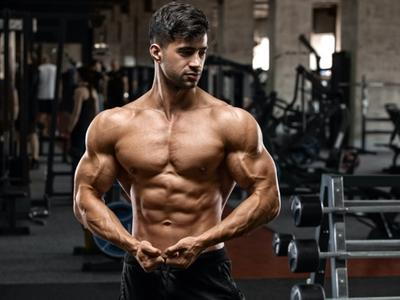 Male body builder checking results of 3-day split workout schedule
