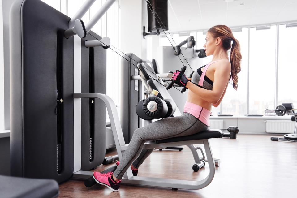 Woman training on home gym machine